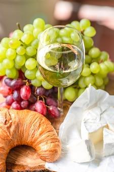 赤と緑のブドウ、チーズ、クロワッサンとワインのグラス。