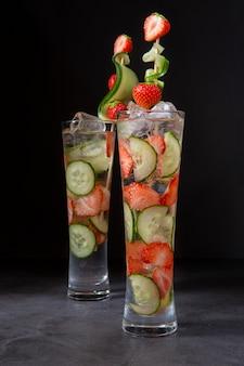 Безалкогольные и освежающие напитки с фруктами в жаркую погоду. огурец, клубничный лед и минеральная вода.