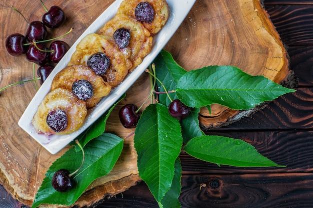 木の板に緑の葉とプレートとチェリーベリーのチェリーソースのパンケーキ