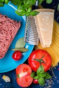 イタリア料理。パスタボロネーゼの準備のための製品。ミンチ肉、トマト、スパゲッティ、バジル、パルメザンチーズ、スパイス