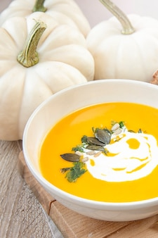 Сезонная еда. супы из тыквы. суп украшен сливочным соусом и тыквенными семечками.