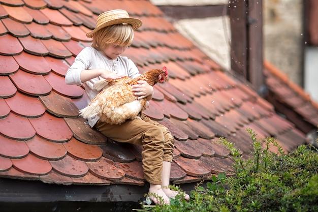 麦わら帽子をかぶった少年がお気に入りの鳥と一緒に屋根に座っています。