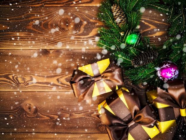 木の板に花輪を捧げる。ラップされたギフトボックス。クリスマス