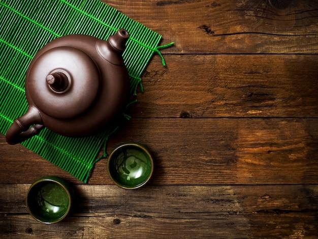 Чайник на зеленой бамбуковой циновке. вид сверху