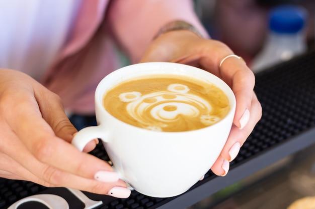 Девушка-бариста предлагает готовый кофе-латте с нарисованным красивым узором в виде медведя