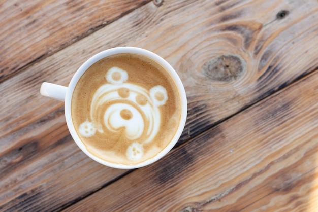 木製のテーブルの上のコーヒーカップ。クマ柄のカプチーノ。上面図