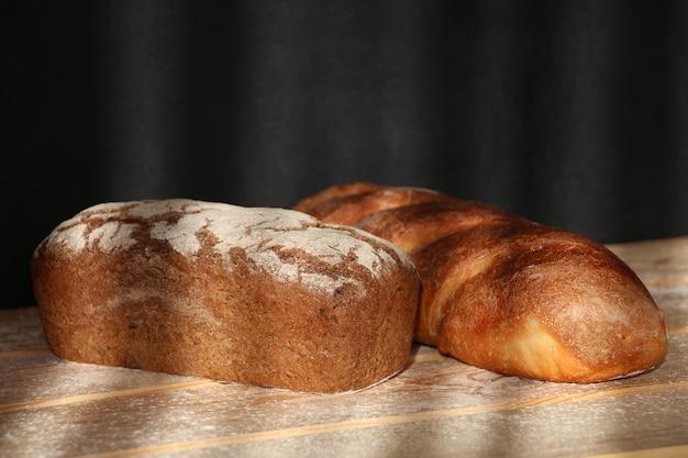Буханка черного хлеба и белый хлеб с мукой на деревянном столе в солнечном свете