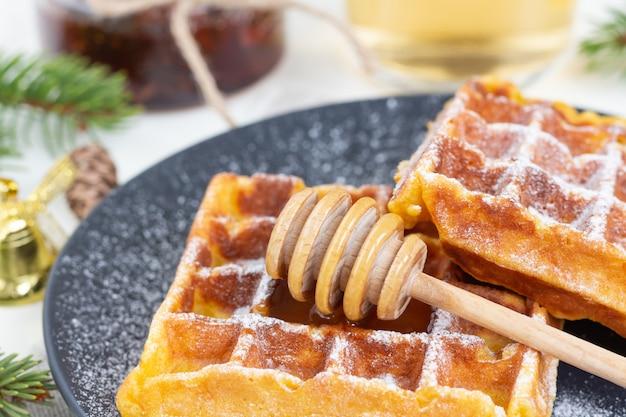 Бельгийские вафли посыпать сахарной пудрой с ложкой меда на черной тарелке.