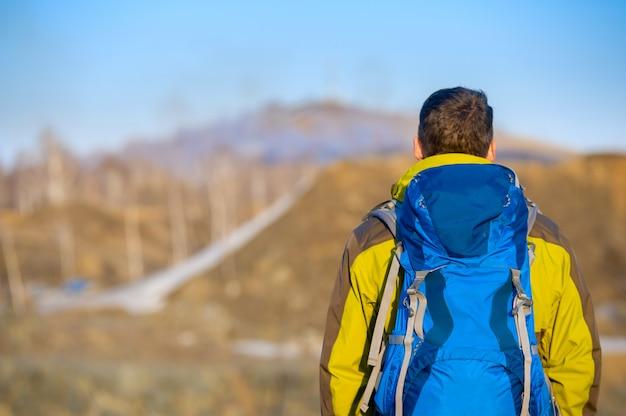 Молодой человек с рюкзаком смотрит вдаль