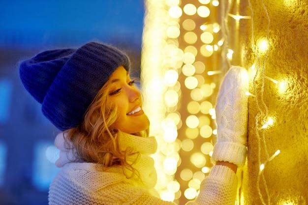 お祝いクリスマスや新年フェアの花輪と休日ライトを持つ女性の笑みを浮かべてください。