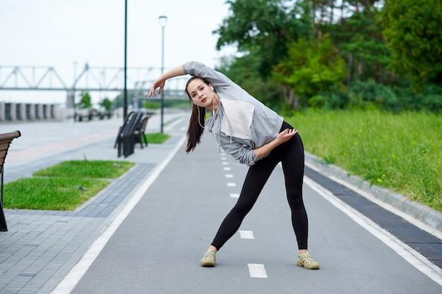 Женщина фитнеса молодая азиатская протягивая ноги после бега. на улице после пробежки