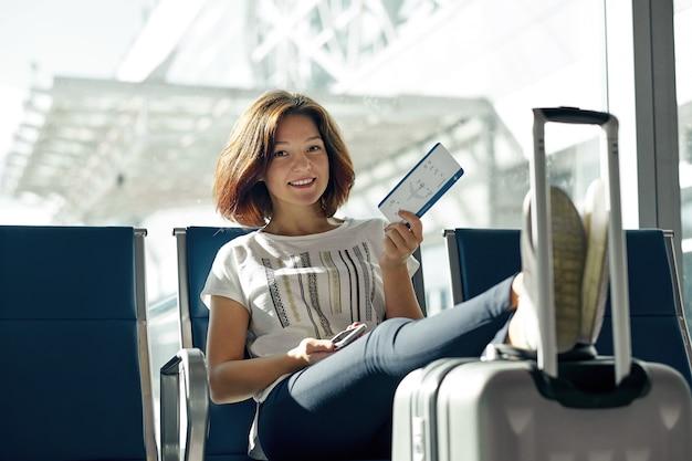 チケットと空港で荷物を持つ女性の笑みを浮かべてください。ターミナルで待っているゲートで手荷物スーツケースと座っている若いカジュアルな女の子と空旅行の概念。