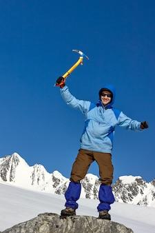 Крупным планом портрет улыбающегося альпиниста с ледорубом на высокой горе