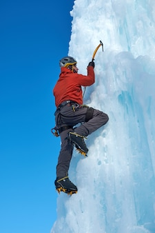 氷の大きな壁を登る氷ツールを持つアルピニスト男。アウトドアスポーツの肖像画。