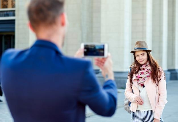 女性が都市ツアーで休暇の写真のポーズします。写真を作る観光客のカップル