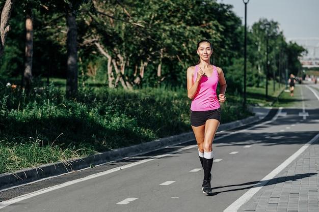 トレーニングセッション中に競馬場で走っている女性。陸上競技のレーストラックで練習する女性ランナー