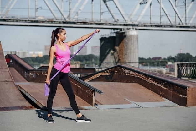 Фитнес женщина делает упражнения на растяжку с резинкой на городской город