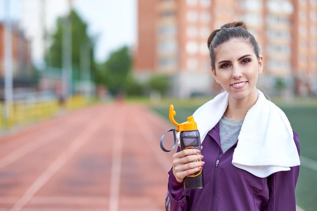 Бегун женщина с полотенцем отдыха и питьевой воды из бутылки после разработки беговой дорожки стадиона