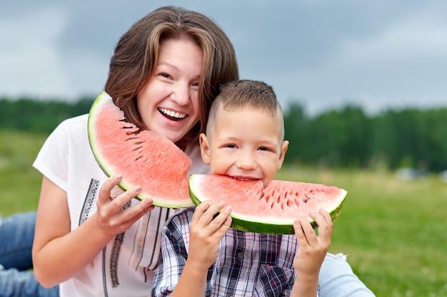 Мать и сын едят арбуз в луг или парк. счастливая семья на пикнике. открытый портрет