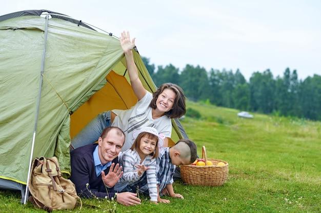 Семья родители и двое детей в лагерной палатке. счастливая мать, отец, сын и дочь на летних каникулах