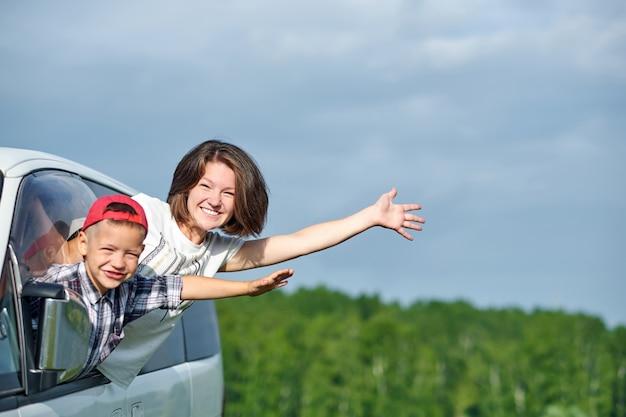 幸せな若い女性と彼女の子供は窓から外を見て。車で旅行する家族
