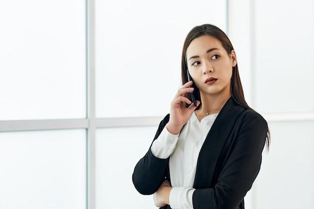 アジアの実業家が電話で話しています。オフィスで美しい女性の肖像画