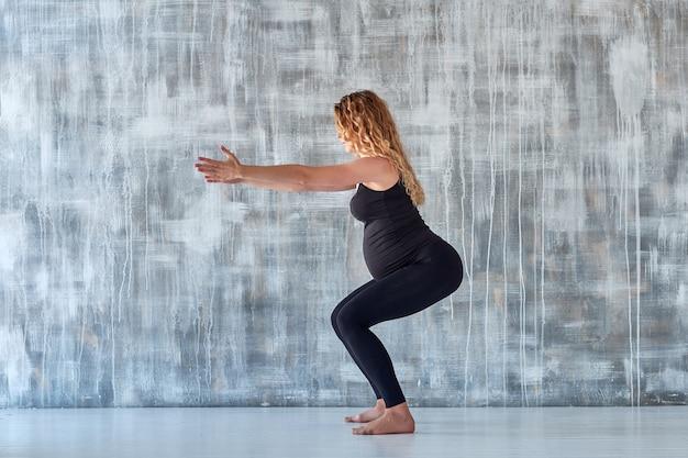 Йога. раздумье йоги беременной женщины практикуя в студии. концепция здорового образа жизни и уход за ребенком