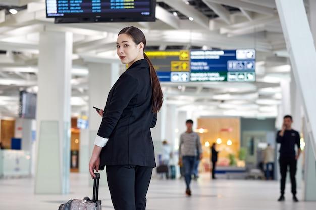 トロリーバッグと空港でアジアビジネス女性、フライトスケジュールを探しているフライトディスプレイの近く