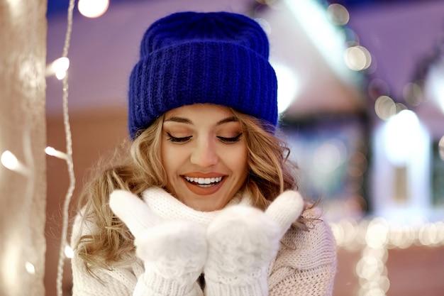 お祝いクリスマスや新年フェアの花輪と休日ライトを持つ女性の笑みを浮かべてください。古典的なスタイリッシュな冬のニットセーターとミトンを着ている女性。エアキス