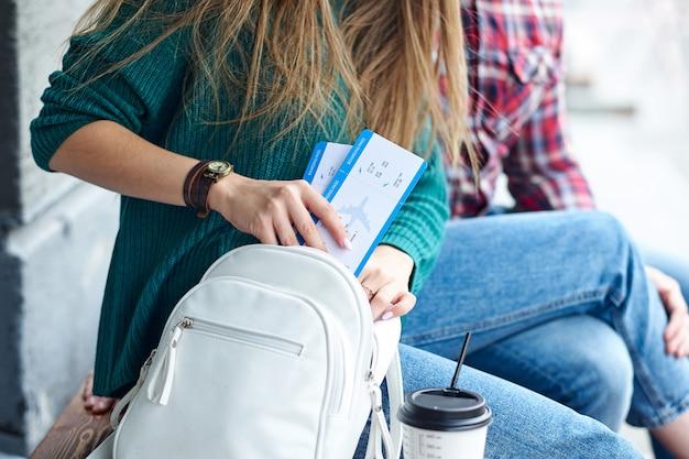 女性の手はバッグに搭乗券を置きました。チケットを持っている手。飛行機と旅行を待っています