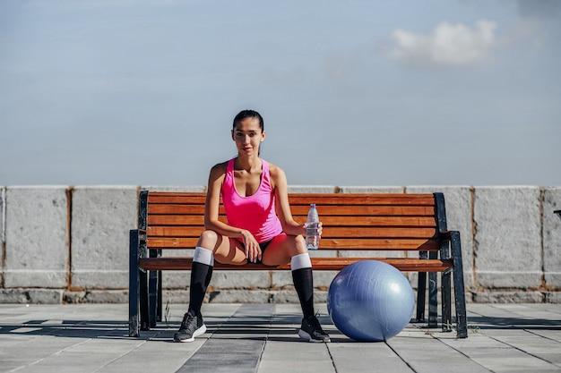 Женщина фитнеса с шариком бутылки и резины подходящим. женская питьевая вода после тренировки на скамейке в городском городе