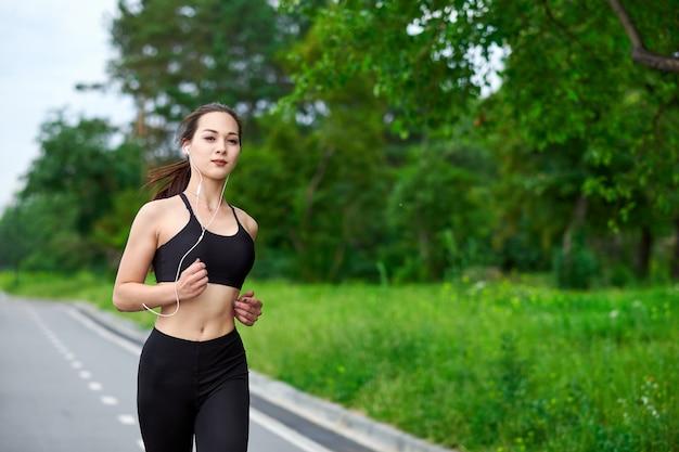 ランニングトラックでアジアの女性を実行しています。朝のジョギング。アスリートトレーニング