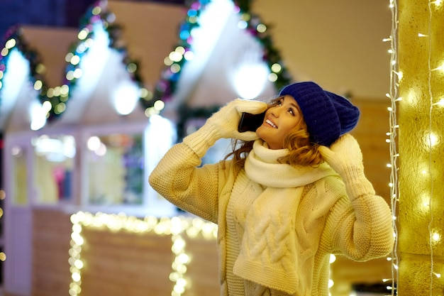 クリスマスや新年を祝う女性の呼び出し。お祝いフェアでスマートフォンを持つ女性