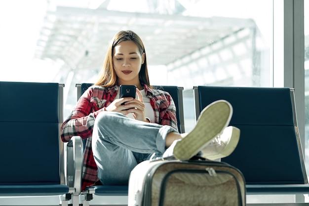 手荷物スーツケースに座っているカジュアルな少女との空気旅行の概念。ターミナルで待っているゲートでスマートフォンで空港のアジアの女性。