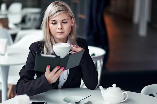 電子書籍を読んで、コーヒーを飲みながらカフェで若い女性