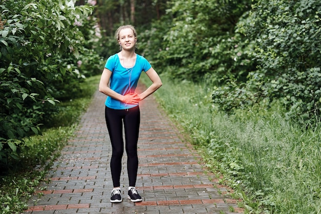Боковая боль - у женщины бегуна боковые судороги после бега. бег женщина с боли в животе после бега потренироваться. спортсменка.