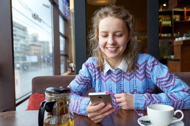 一杯のコーヒーとカフェのコーヒーショップでスマートフォンを使用して笑顔の女性