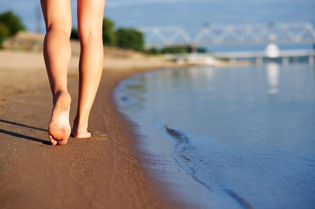 女性の足と足の都市背景の海の水とビーチの砂の上を歩く