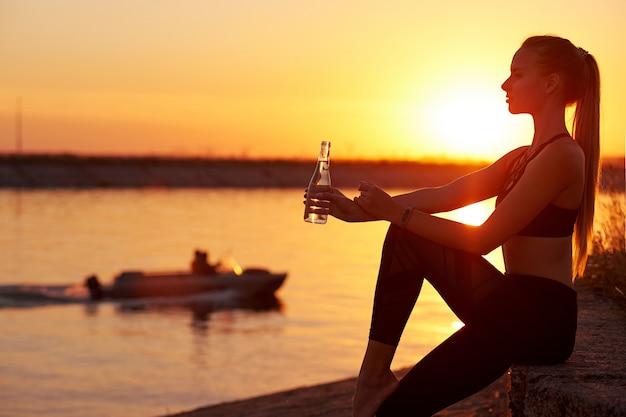 シルエット女性は、ビーチでの実行またはヨガの後、ボトルから水を飲む。夕暮れ時のフィットネス女性のプロフィール、スポーツとリラクゼーションのコンセプト。背景にボートします。