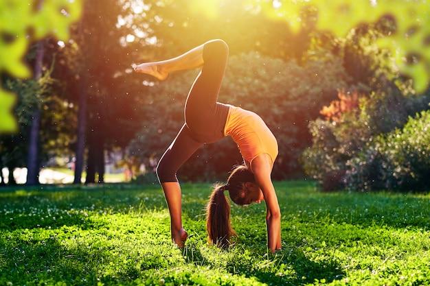 ヨガ。ブリッジエクササイズ。若い女性のヨガの練習やダンスや公園で自然の中でストレッチ。健康ライフスタイルコンセプト