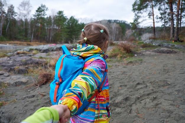 私に従ってください-旅行で彼女に従うか、または野生の自然の中を歩くことを母親に望んでいる子供の娘