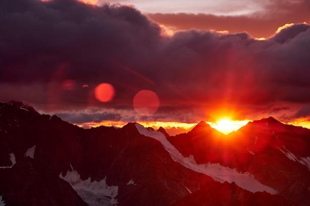 山の夕日。山の雪のピークと雲に赤い太陽の反射。アルタイ、ベルーハ地区
