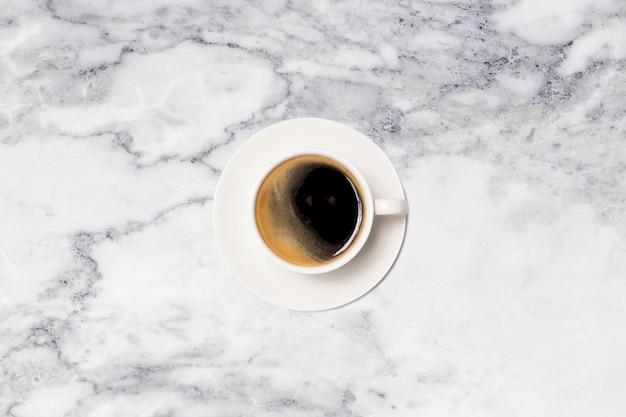 Кофейная чашка на мраморном столе сверху.