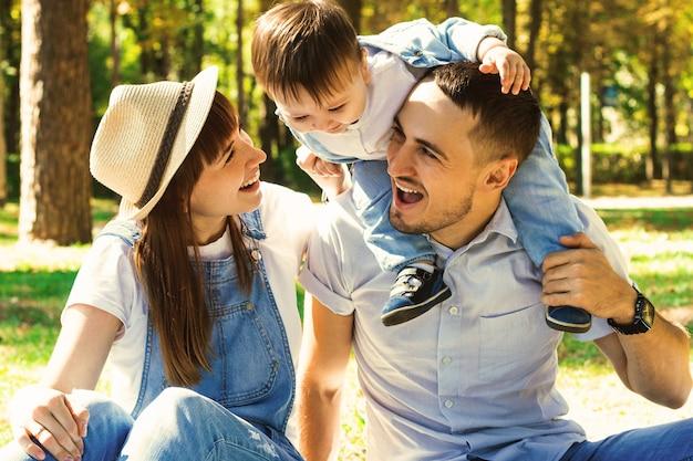 ピクニックで家族。公園で楽しんで幸せな美しい家族。子供は男の肩に座っています。