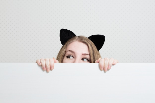 彼女の頭の上の猫の耳を持つ若い女性は白い旗から覗いて、よそ見