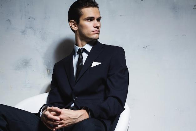 白い汚れた背景に白い椅子に座っている黒のビジネススーツの深刻な男。スタジオ撮影
