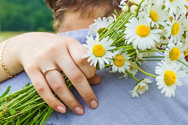 花束カモミールと彼女の指に婚約指輪を持つ女性の腕のクローズアップ