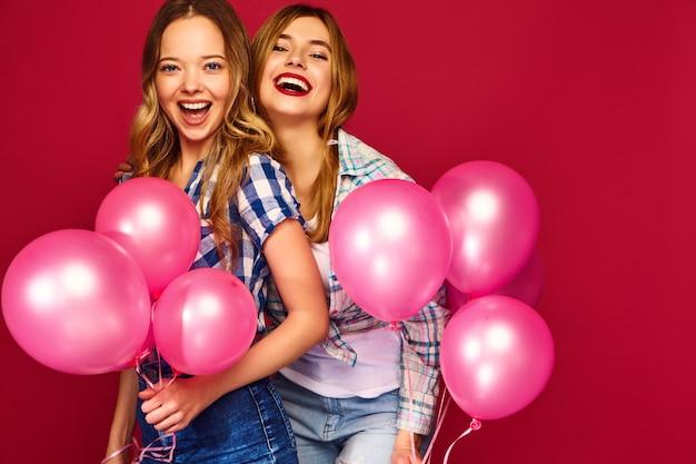 大きなギフトボックスとピンクの風船でポーズの女性
