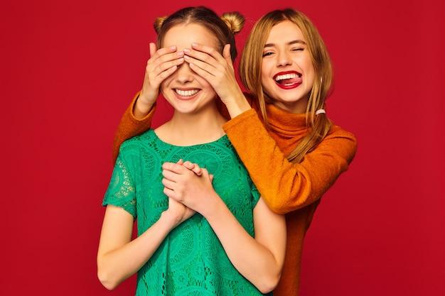 彼女の友人に手で目を覆っている笑顔の女性