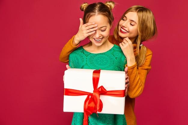 彼女の友人の目を覆って大きなギフトボックスを与えるモデル